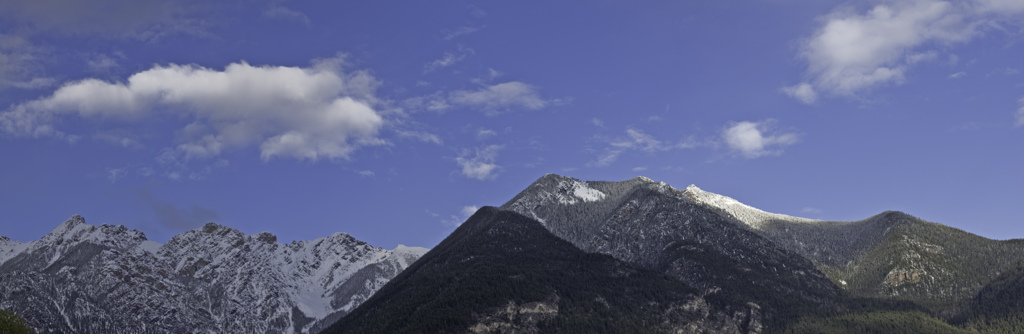 Panorama of mountains, with blue sky and a cloud